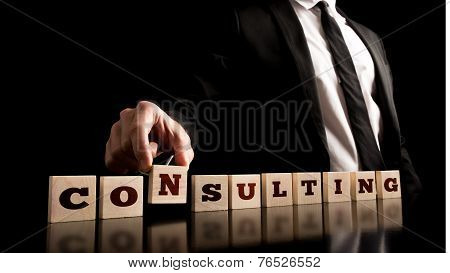 Consultant Arranging Wooden Pieces With Consultingtext