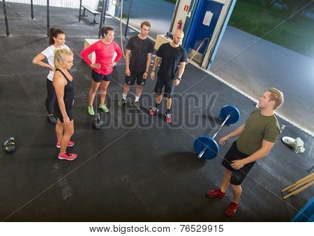 High angle view of young male trainer talking to athletes in gym