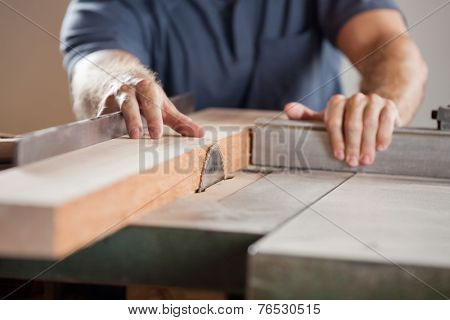 Midsection of carpenter cutting wood with tablesaw in workshop