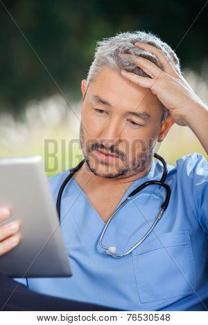 Tensed male caretaker using tablet PC in nursing home porch