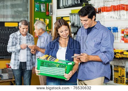 Happy couple buying tools at hardware store with customers in background