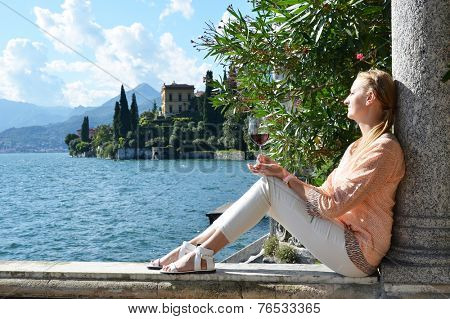 Girl with a wineglass at the Como lake, Italy