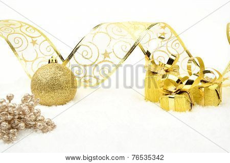 Golden Christmas Gifts,baubles Ribbon And Rowan On Snow