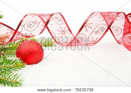 Red Christmas Bauble And Needles Fir And Ribbon On Snow