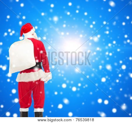 christmas, holidays and people concept - man in costume of santa claus with bag from back over blue snowy background