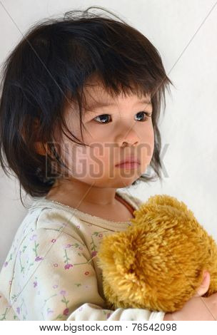 Small almost two years old child portrait. Teddy bear in hand. Mixed ethnicity, chinese with european.