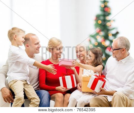 family, holidays, generation and people concept - smiling family with gift boxes sitting on couch over living room with christmas tree background