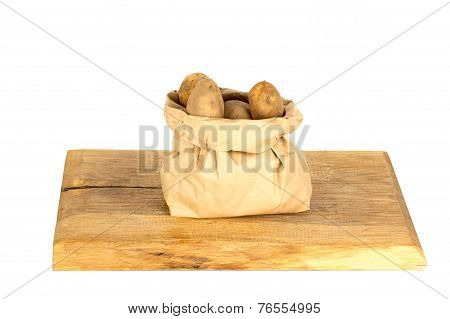Unwashed Potatoes In A Paper Bag Isolated On White