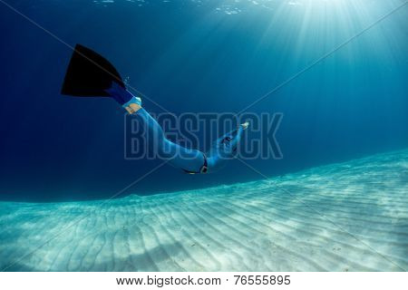 Lady free diver swimming in monofin over sandy bottom