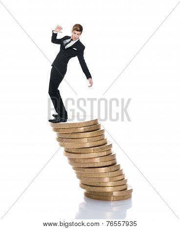 Businessman Balancing On Stacked Coins