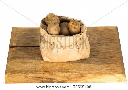 Unwashed Potatoes In A Paper Bag Islated On White