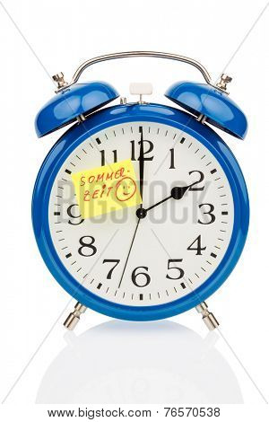 an alarm clock with a note as a reminder to the uhrumstellung to summer time