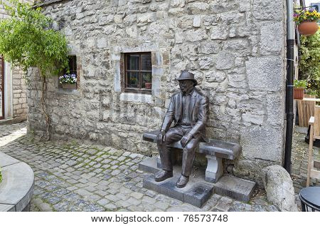 Monument Of A Man In A Hat Sitting On A Bench In Durbuy