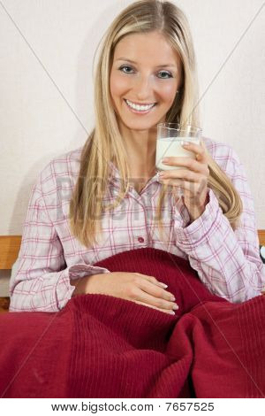 Woman In Pajama In Bed With Glass Of Milk