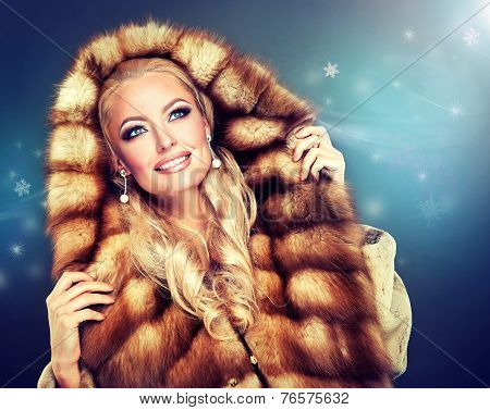 Winter model girl in luxury fur coat with a hood .