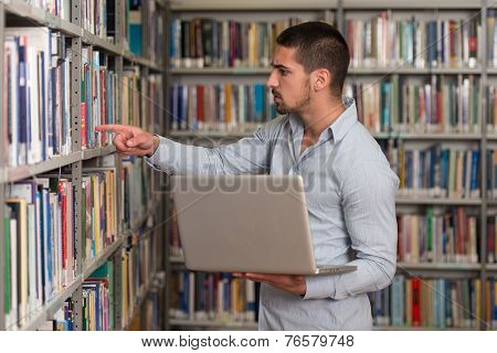 Happy Male Student With Laptop In Library