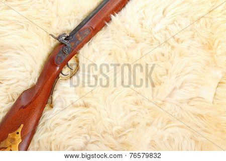 Close up of hunting gun on a sheep fur.