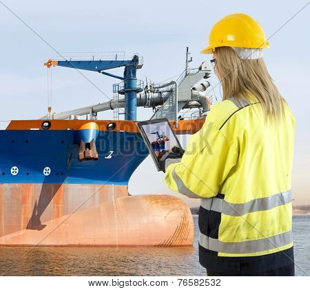 Female quality assurance manager takinga picture of a dredging vessel with her tablet, looking for specific details during an inspection round