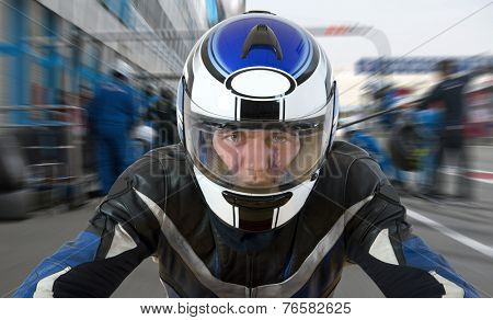 Motor racer leaving the pit during a race, accelerating from the pits lane, seen from the bike's perspective
