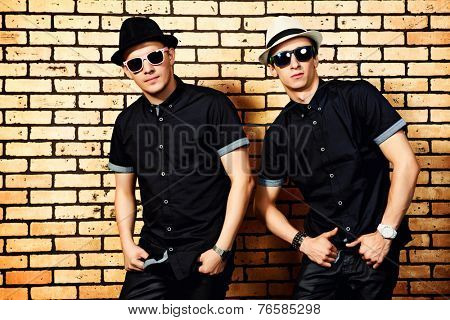 Two handsome men in black shirts and black sunglasses against brick wall.