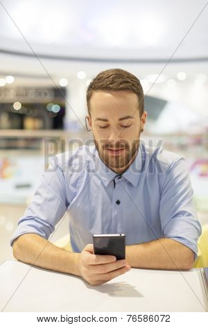 Smiling Businessman with electronic device on hand, blurred background of indoor shopping mall