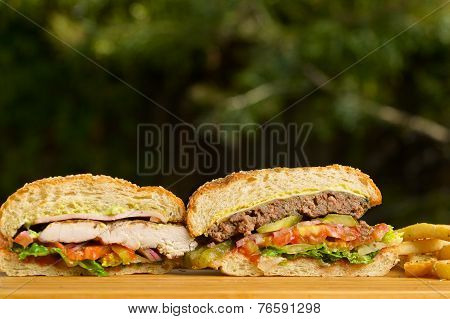 Two cutted burgers with melted cheese and thick succulent ground beef patty, grilled chicken, lettuc