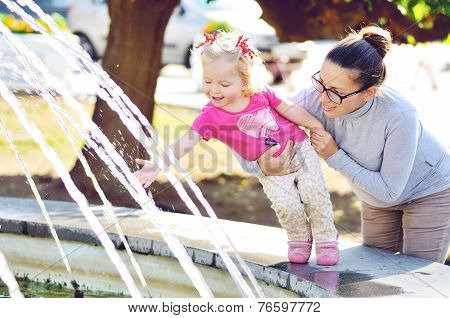 Mother With Baby Girl Near The Fountain
