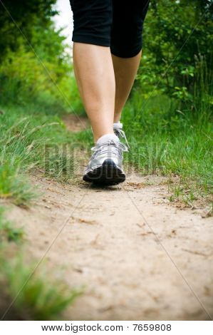 Woman Walking Cross Country on Trail