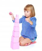stock photo of inflatable slide  - charming little girl collects in the Montessori classroom pyramid isolated on a white horse - JPG