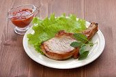 foto of pork cutlet  - White plate with fried pork cutlet lettuce and red hot sauce on the wooden table - JPG