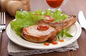 picture of pork cutlet  - White plate with fried pork cutlet lettuce tomato and red hot sauce on the wooden table - JPG