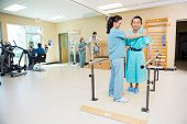 stock photo of physical therapist  - Female physical therapists assisting patients in hospital gym - JPG