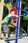 stock photo of chute  - active little boy climbing on the playground - JPG
