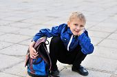 foto of schoolboys  - schoolboy with backpack is sitting and smling - JPG