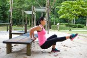 foto of dipping  - Sporty woman doing dips on left leg in outdoor exercise park - JPG