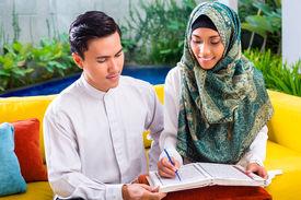 stock photo of muslim man  - Asian Muslim man teaching woman reading Koran or Quran in living room - JPG