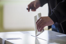 picture of insert  - Hand of a person casting a ballot at a polling station during voting - JPG