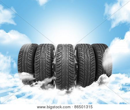 Wedge of new car wheels. Background is sky with clouds and stripes
