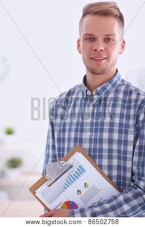 Smiling businessman with folder sitting in the office