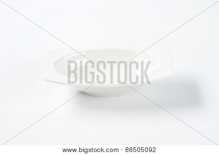 white oval bowl with rim on white background