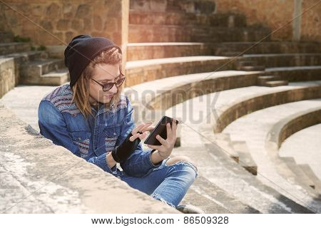 Guy Sitting On A Staircase With Tablet Warm Filter Applied