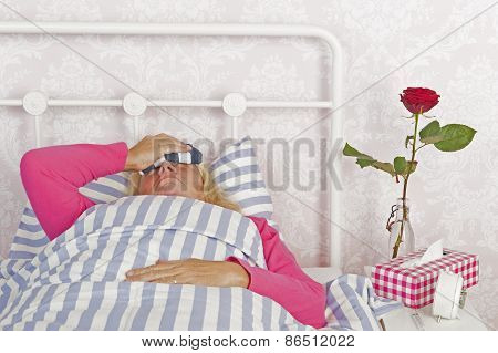 Woman With Headache Lying In Bed