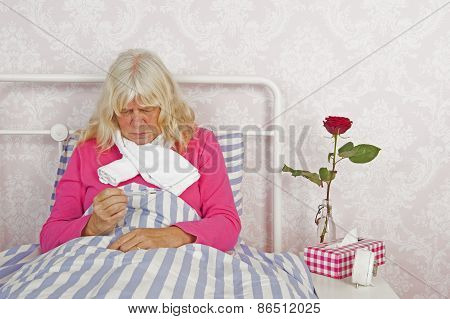 Woman With Thermometer Sitting In Bed