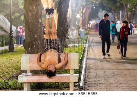 HANOI, VIETNAM, DECEMBER 15, 2014: A man is practicing Yoga on a public bench in evening at the city center's Hoan Kiem lake in Hanoi city, Vietnam.