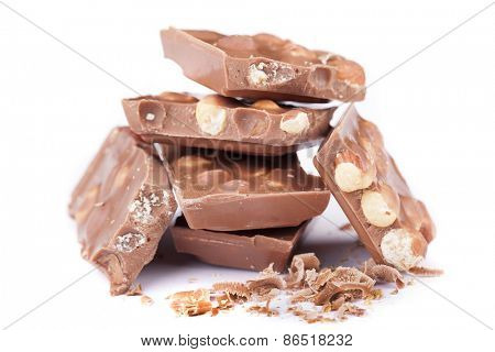 Milk chocolate with hazelnuts on white background