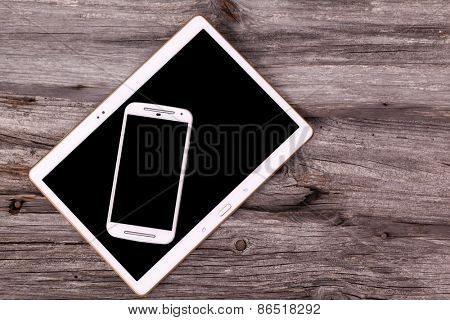 Digital tablet and smart phone on wooden background