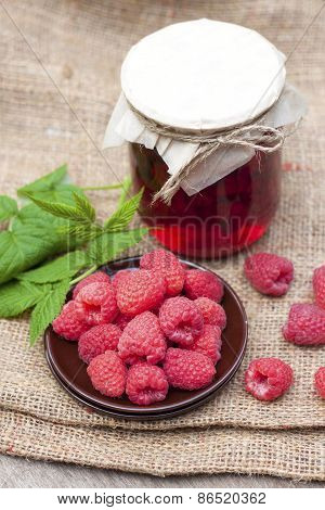 Raspberry Preserve In Glass Jar And Fresh Raspberries On A Plate