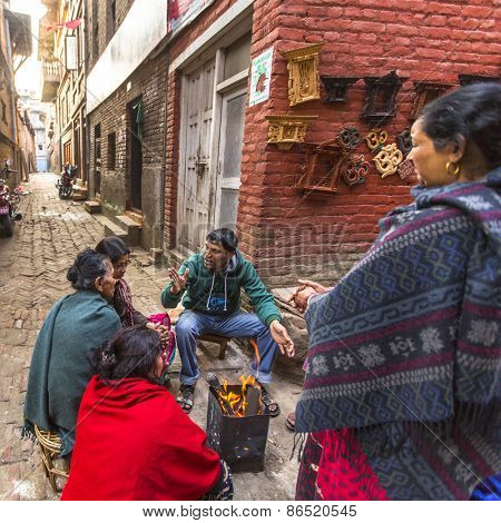 BHAKTAPUR, NEPAL - CIRCA DEC, 2013: Unidentified local people sit in the street. The caste system is still intact today but the rules are not as rigid as they were in the past.
