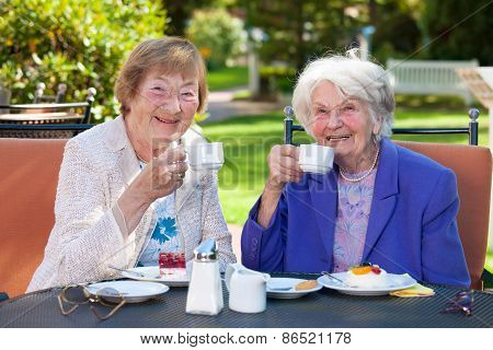 Elderly Best Friends With Coffee At Outdoor Table