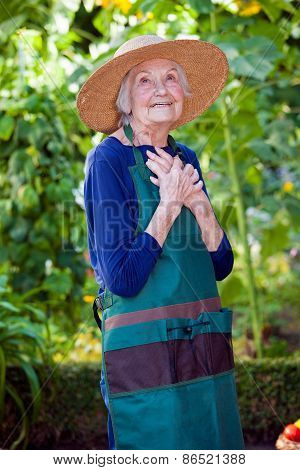 Thoughtful Senior Woman In Garden Hat And Apron